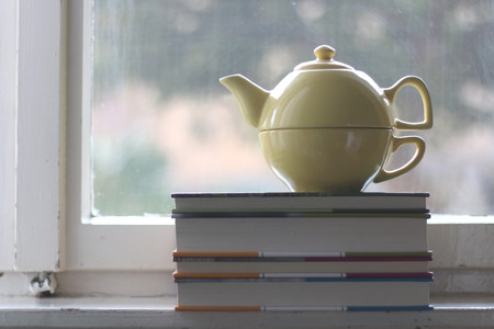 tea cosy: Teapot and pile of old books on rustic window. Selective focus. Stock Photo