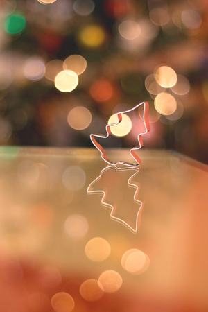 cookie cutter: Cookie cutter shaped like little Christmas tree. Beautiful colorful bokeh in the background.