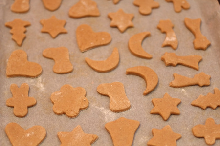 bell shaped: Honey cookies shaped like various Christmas symbols, ready for oven. Selective focus. Stock Photo