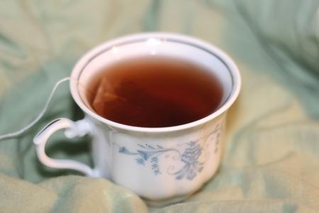 tea bag: Cup of tea with tea bag on the bed.