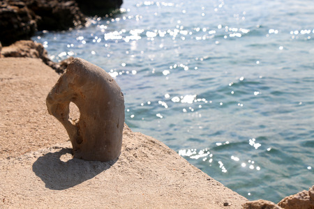 mooring bollard: Small, artistically shaped, stone made mooring bollard by the sea. In Vela Luka, Korcula island, Croatia. Selective focus. Stock Photo