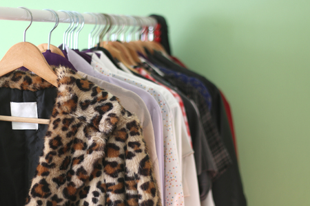 Clothes rack with colorful clothes. Fake leopard fur coat in the foreground. Selective focus, green background.