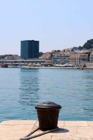 mooring bollard: Rusty mooring bollard on Riva Promenade in Split, Croatia. The West Coast view in the background. Stock Photo