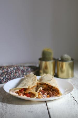 comidas rapidas: Dos envolturas de tortilla rellena de pollo y verduras diversas rojos y pimientos verdes, cebolla morada, granos de caf� y ma�z, con blanco salsa de crema. mesa de madera blanca con la servilleta de flores y cactus. Foto de archivo