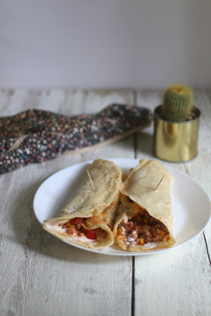 healthier: Two tortilla wraps filled with chicken and various vegetables red and green peppers, purple onion, brown beans and corn, with white cream sauce. White wooden table with floral napkin and cactus.