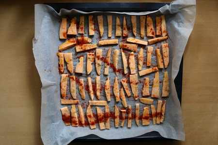 healthier: Sweet potato slices organized in a baking pan, before baking. With origano and sweet pepper powder on top. Top view.