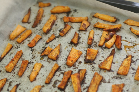 healthier: Baked sweet potato fries with olive oil, allspice and origano. Selective focus. Stock Photo