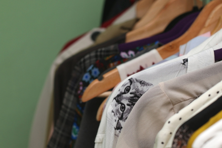 blouses: Various patterned blouses on the hangers. Focused on the cat-patterned shirt. Selective focus.