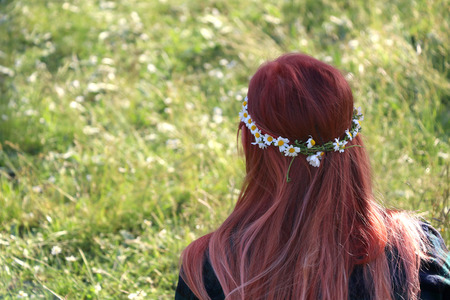 Fille méconnaissable portant la couronne de fleurs de marguerite dans ses cheveux. Mise au point sélective