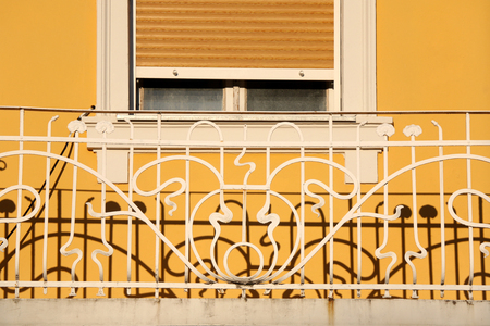 decorative balcony: Decorative fence on the balcony creating interesting shadow. Yellow building exterior.