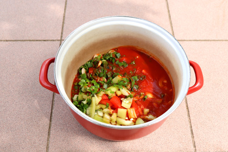 scallions: Sliced tomatoes, green peppers, parsley and scallions with tomato sauce, in a pot.