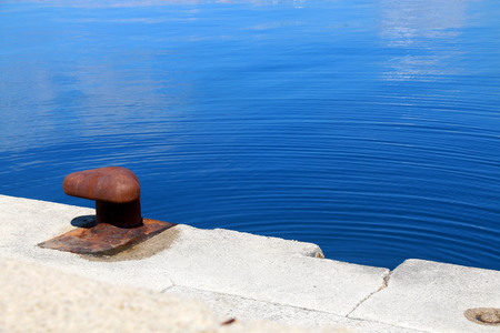 mooring bollard: Rusty mooring bollard and bright blue sea.