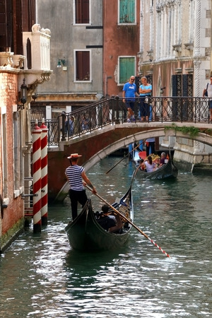 gondolier: Venice, Italy - August 20, 2016: Gondolier driving a gondola in the canal in Venice - typical scene in Venice.