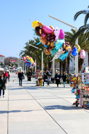 public space: Split, Croatia - March 17, 2016: Colorful balloons for sale on Riva Promenade in Split, Croatia. Bunch of people enjoying a walk in the background. Split has become a popular touristic destination. Riva is the most popular public space for both locals and