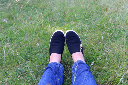 without legs: Legs in jeans and black slip-ons in the grass. Selective focus. Stock Photo