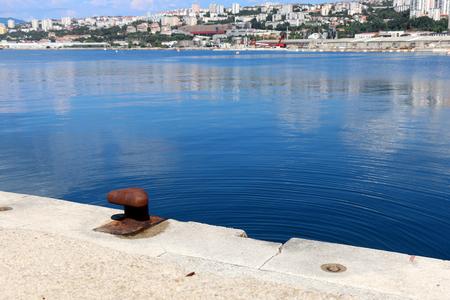 mooring bollard: Rusty mooring bollard and bright blue sea. Rijeka waterfront in the background. Rijeka is selected as the European Capital of Culture for 2020. Stock Photo