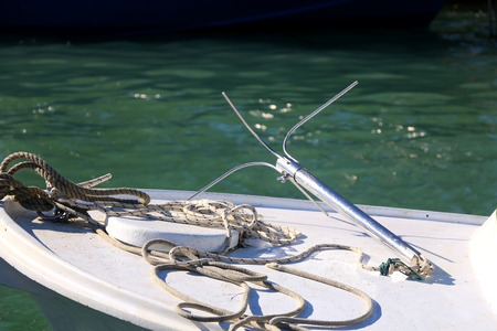 nautical equipment: Nautical equipment on a small wooden fishing boat: ropes and modern anchor. Focused on the ropes, shallow depth of field. Stock Photo