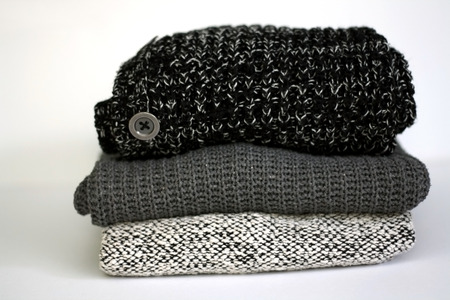 Stack of three chunky grey sweaters. Selective focus. Stock Photo