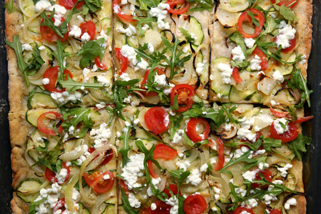 Vegetarian pizza in a pan, with mozzarella, onion, garlic, zucchini, cherry tomato, cottage cheese and salad rocket. Top view. Reklamní fotografie