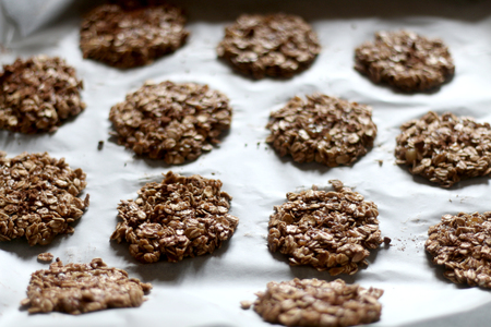 Simple cookies prepared with three ingredients: oatmeal, mashed bananas and cocoa powder, before baking. Top view, selective focus. Stock Photo