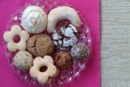 Plate of various cookies on pink napkin, top view.