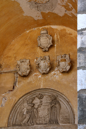 relievo: Catholic relief and historic coats of arms on a building exterior in Dubrovnik, Croatia.