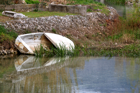 grounded: Small old boat abandoned in a river. In Solin, Croatia. Selective focus. Stock Photo