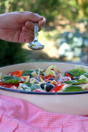 Pouring olive oil in a bowl of Greek salad. Selective focus. Stock Photo