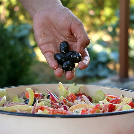 Putting olives in a bowl of Greek salad. Selective focus. Stock Photo