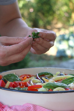 Putting parsley in a bowl of Greek salad. Selective focus.