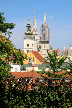 Love locks on Strossmayer Promenade in Zagreb Upper Town. Zagreb Cathedral and St. Mary Church in the background. Stock Photo