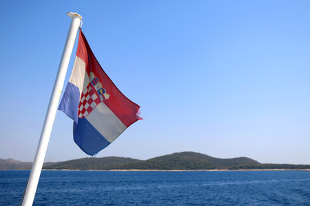bandera croacia: Croatian flag on a boat, blowing in the wind. Beautiful coast in the background. Selective focus. Foto de archivo