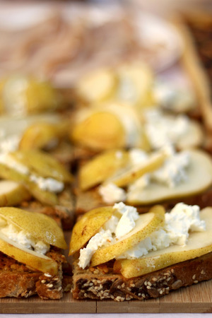 Slices of whole wheat bread with goat cheese and pears. Selective focus. Stock Photo