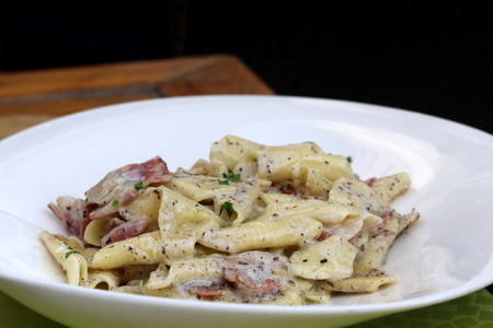 Creamy pasta with bacon and truffles. Traditional food in Slovenia and Croatia. Selective focus. Stock Photo