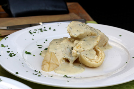 Traditional Slovenian meal called Strukelj - rolled dumpling filled with cheese and creamy Gorgonzola cheese sauce. Selective focus. Stock Photo