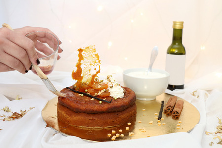 Dried apricot cake with mascarpone frosting and grape syrup, decorated for Christmas. Unrecognizable person glazing the cake with syrup. Selective focus. Stock Photo