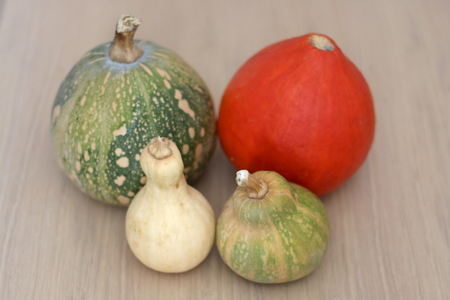 Various pumpkins on a wooden table. Selective focus.