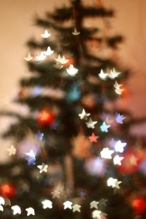 Defocused Christmas tree with star shaped bokeh. Festive holiday background. Imagens