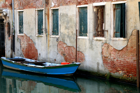 Old wooden boat in canals of Venice, Italy. Typical Venetian architecture in the background. Selective focus. 스톡 콘텐츠