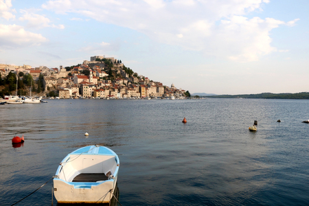 Small rusty boat with a view of Sibenik in the background. Sibenik is popular summer travel destination.