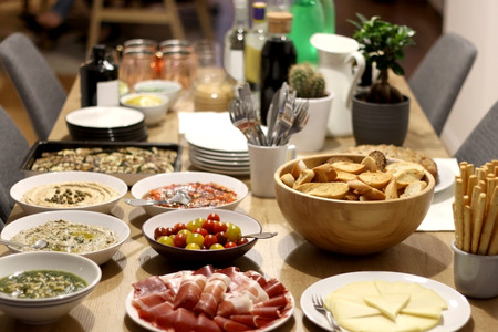 Various food served on a table: prosciutto, pesto, baba ganoush, tuna pate, roasted pepper and eggplant, cheese and toasted bread. Selective focus.