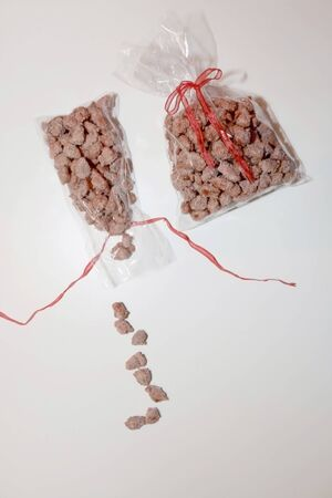 Two bags of homemade candied almonds with red ribbons on white background. Selective focus. 写真素材