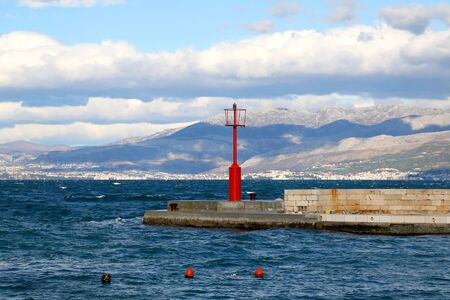 Small red lighthouse on the pier in Sutivan, island Brac, Croatia. Windy and cloudy weather, beautiful landscape.
