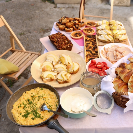 Table with various brunch food: goat cheese and pear sandwiches, ham, croissants, scrambled eggs, mushroom tart, blueberry muffins, banana bread, cream cheese and hazelnut spread. Top view.