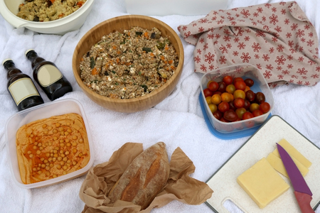 Picnic blanket with various food: bread, buckwheat and vegetable salad, hummus, cheese, cherry tomatoes, pastry, focaccia and galette. Selective focus.