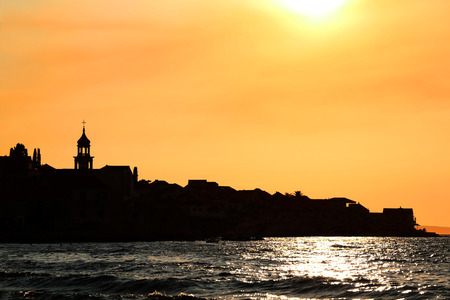 Sunset over Sutivan, small town on island Brac, Croatia. Silhouette view of landmark baroque bell tower. Banco de Imagens