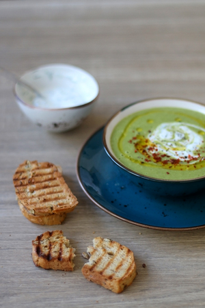 Creamy vegetable soup with kale, cabbage, celery and millet, decorated with olive oil, yoghurt sauce and chilli flakes. Served with toasted bread and lemony yoghurt sauce. Selective focus. Фото со стока