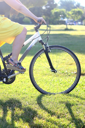 Young woman riding a bike in nature. Close-up of her legs and wheels. Beautiful vibrant sunlight. Selective focus.