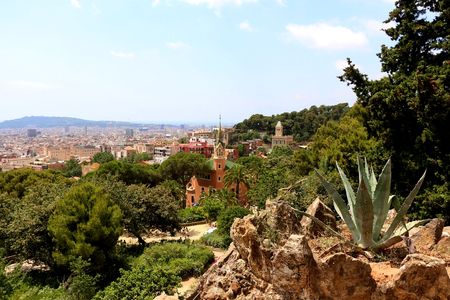 Aerial view of Barcelona from Park Güell with The Gaudi House Museum in the foreground.