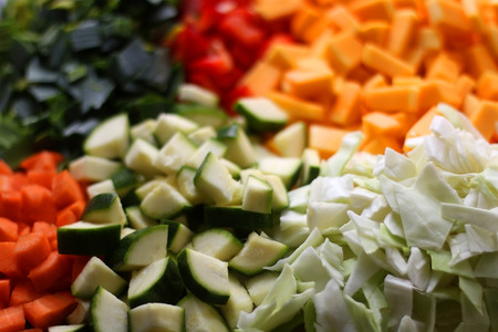 Various chopped vegetables: butternut squash, cabbage, red pepper, courgette, leek and carrot. Top view, selective focus.